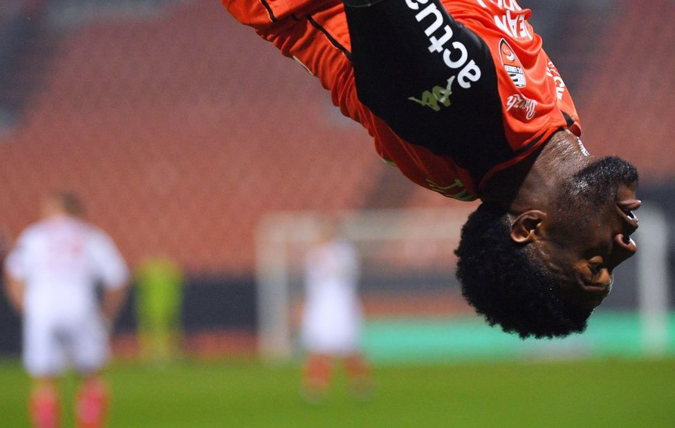 A man somersaults in his football strip.