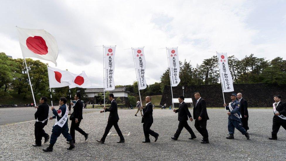 Hombres japoneses marchan con la bandera nacional cerca del palacio imperial.