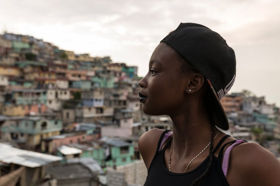 Ckimy, 16, looks out from a rooftop onto the colourfully painted houses of Jalousie
