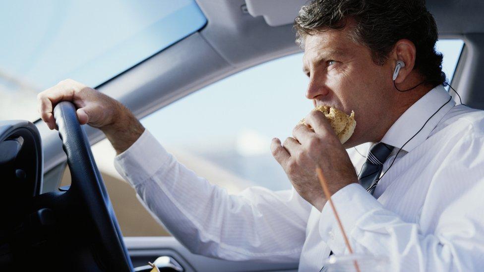 Un hombre conduce un auto mientras come una hamburguesa y escucha por un audífono