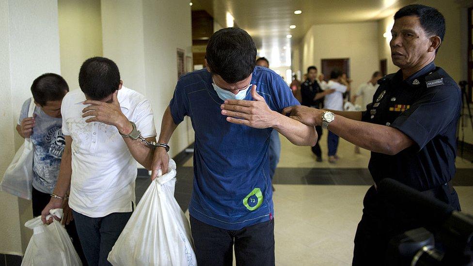 Los tres hermanos se cubren la cara en Malasia.