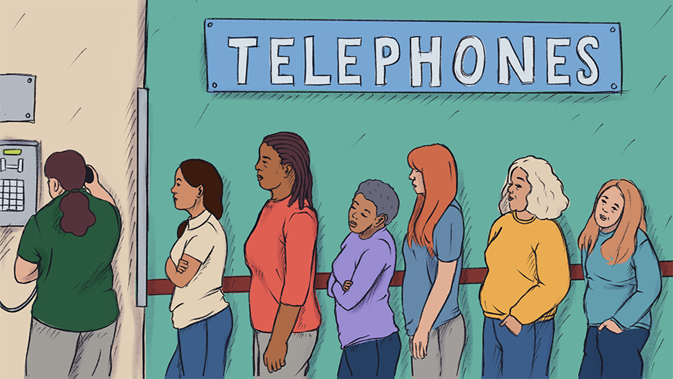 queue of women waiting to use a pay phone in prison