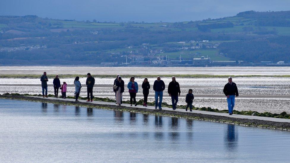 People walking across a marina