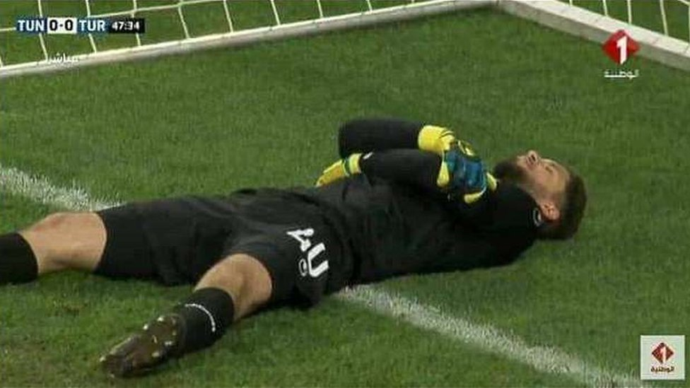 Tunisia's goalkeeper Mouez Hassen lays on the ground