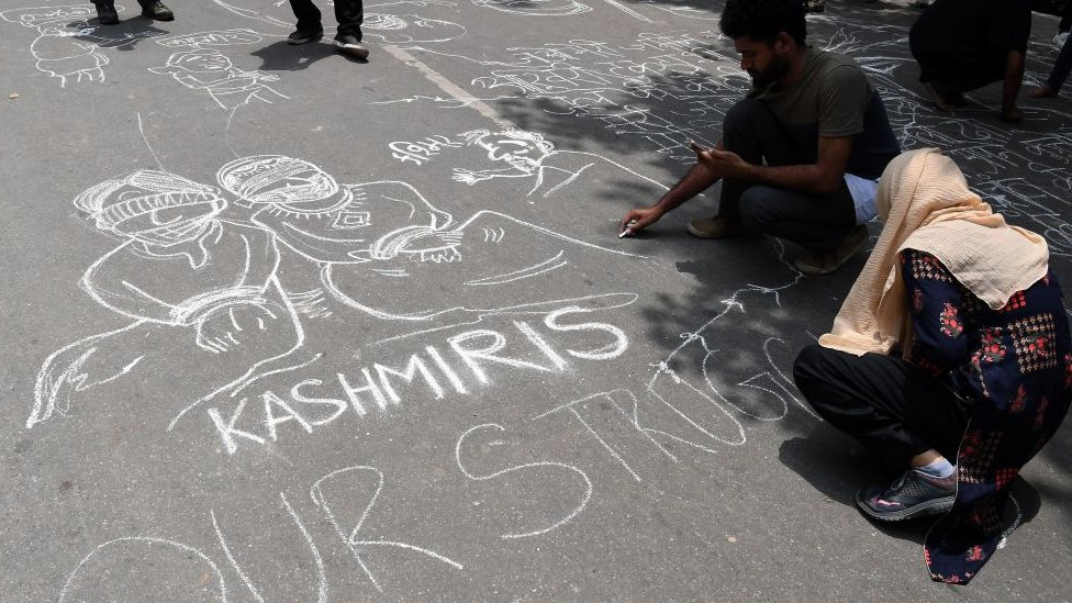 Communist Party of India (CPI) activists draw graffiti on the ground during a protest in New Delhi on August 7, 2019, in reaction to the Indian government scrapping Article 370 that granted a special status to Jammu and Kashmir.