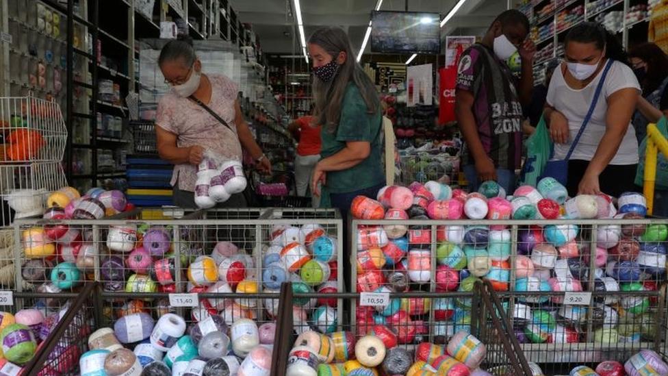Diversas pessoas de máscaras em loja de comércio popular