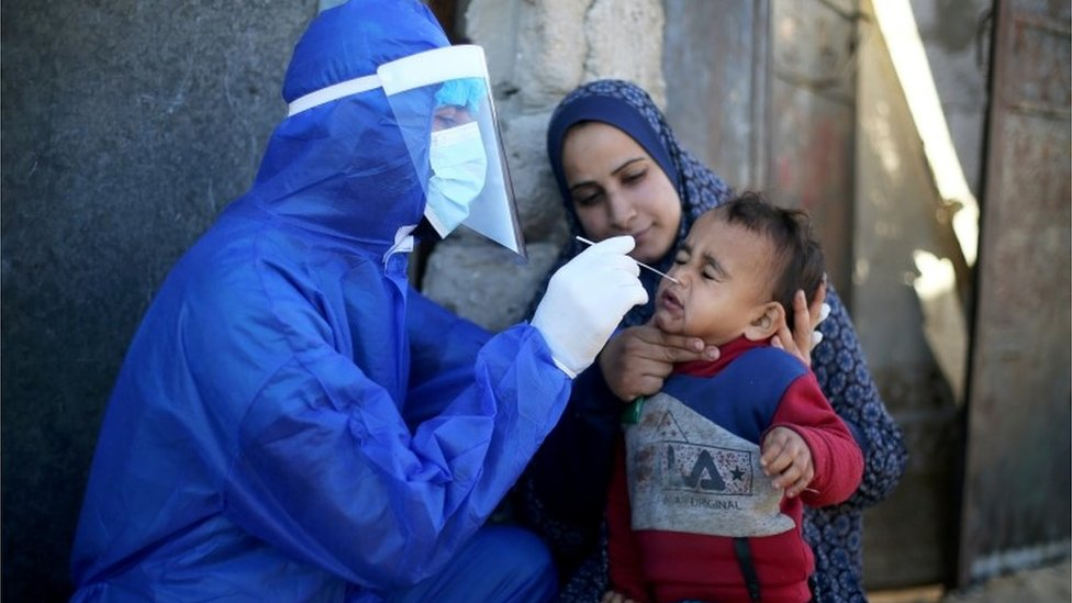 مسؤول طبي فلسطيني يجري مسحة لفيروس كورونا لطفل
