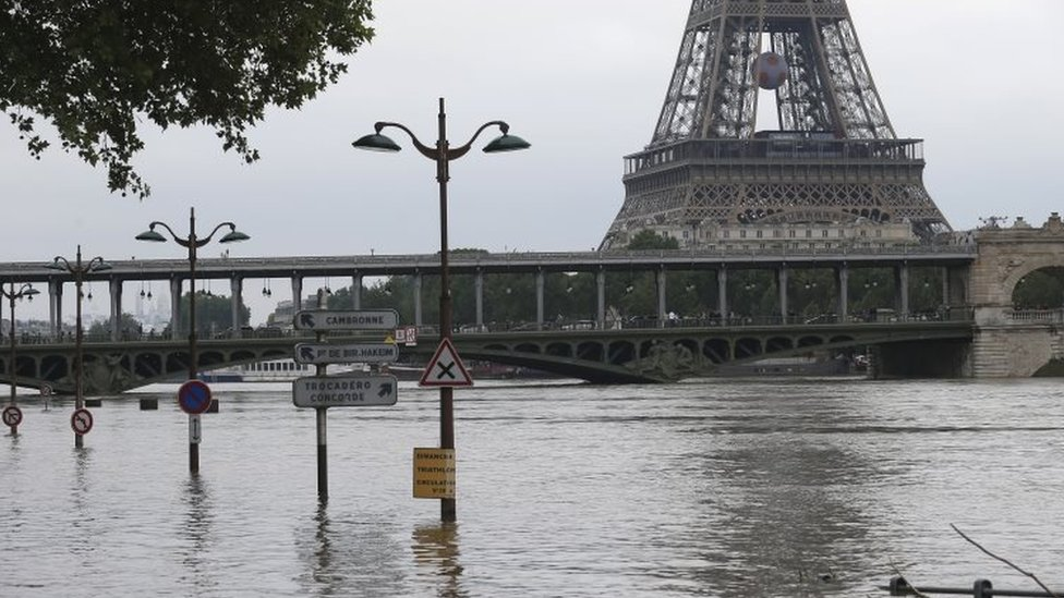 Road signs emerge on the banks of the Seine river next to the Bir Hakeim bridge and the Eiffel Tower during floods in Paris (04 June 2016)