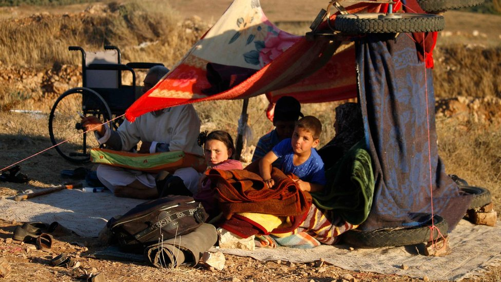 Displaced Syrians from the Deraa province wait in a makeshift camp near the town of Nassib to cross the Jordanian border (1 July 2018)