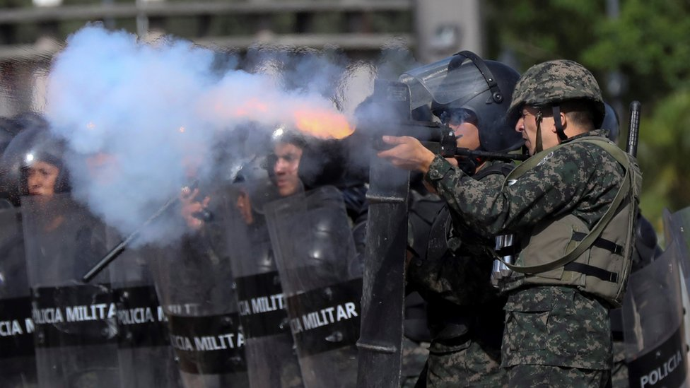 Military police officers shoot tear gas at students during clashes, in Tegucigalpa