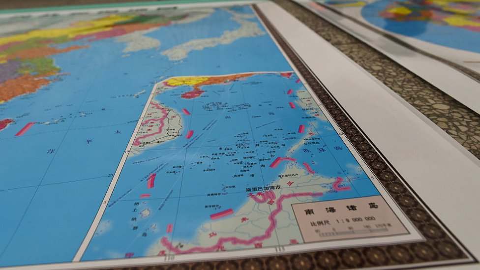 In this photo taken on June 15, 2016 a vendor stands behind a map of China including an insert with red dotted lines showing China's claimed territory in the South China Sea