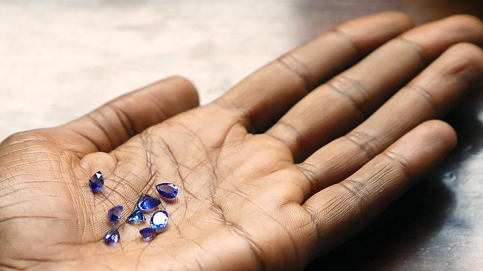 An outreached palm with tanzanite stones on it