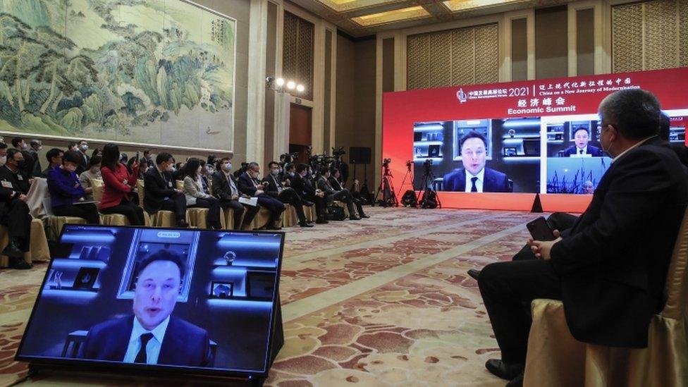 Screens show Elon Musk, CEO of Tesla