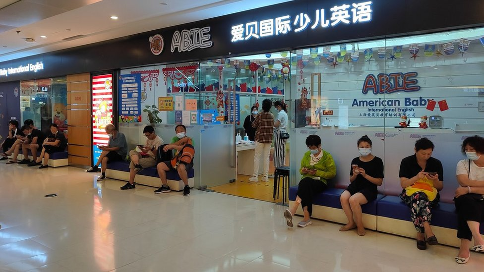 Parents wait outside a children's English early education training store in Shanghai, Aug. 20, 2021.