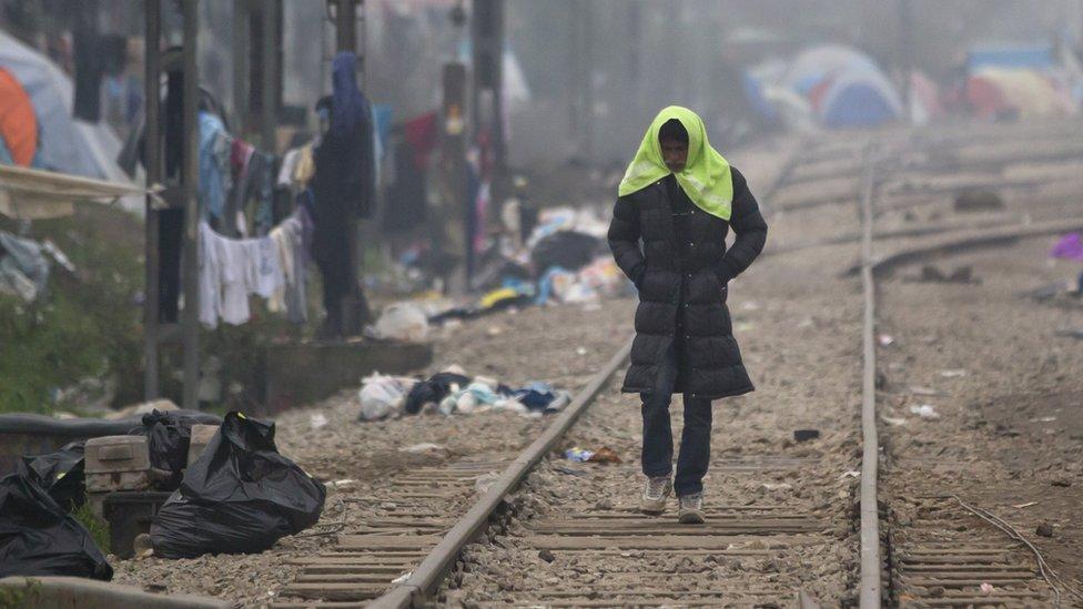 A migrant man walks on railway tracks in Greece