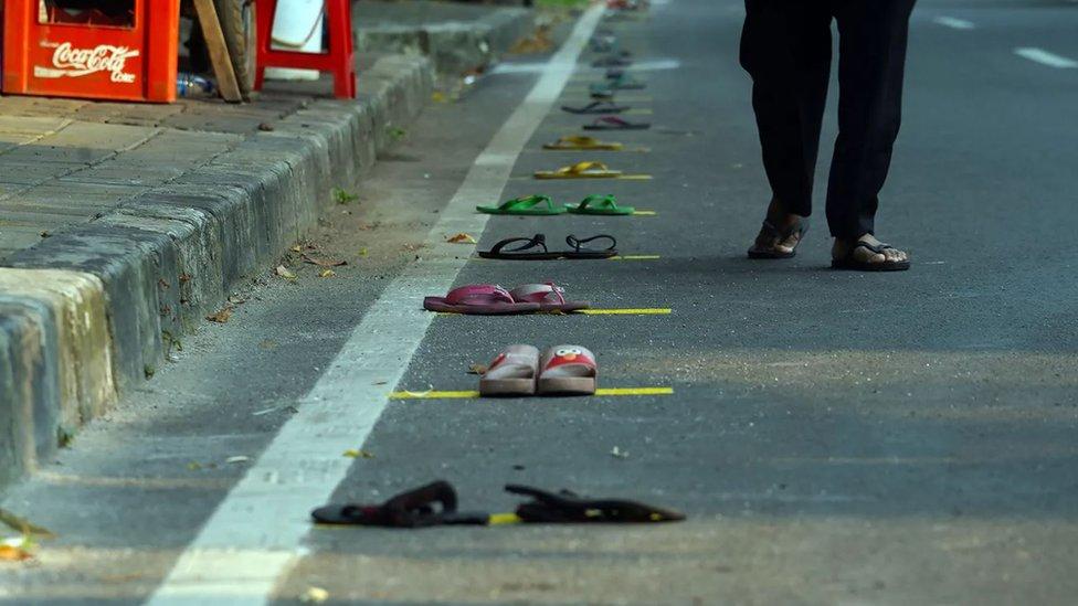 Várias sandálias espalhadas pela rua
