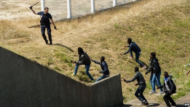 A French policemen trying to keep a group of migrants off a road near Calais