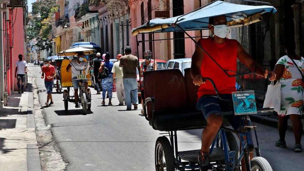 Pessoas caminham em uma rua de Havana