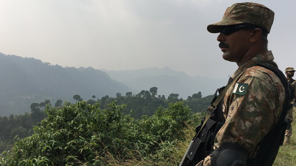 A Pakistani soldier stands guard in the mountainous region near the LOC.