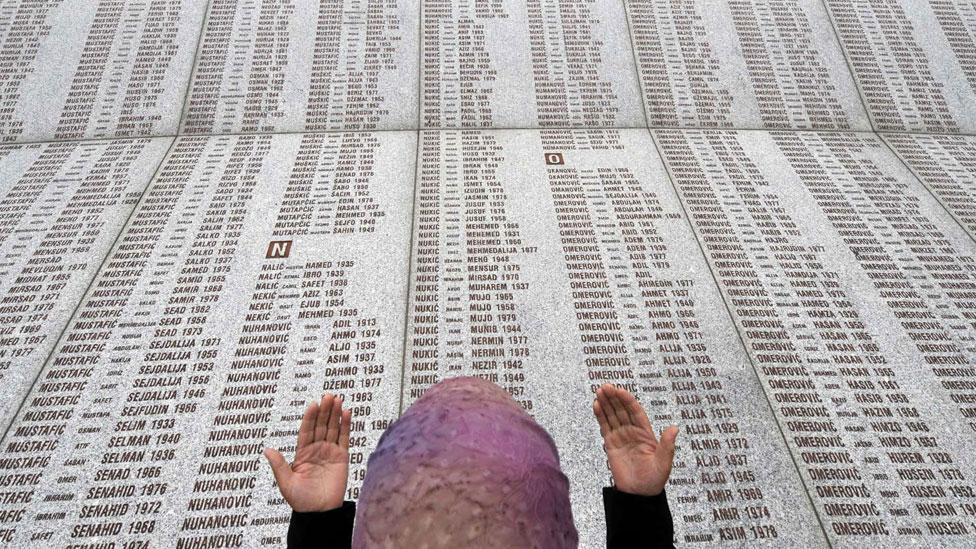 Una mujer llora frente a l memorial con los nombres de las víctimas de Srebrenica