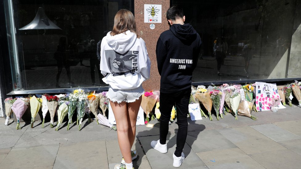 """People wearing Ariana Grande sweatshirts look at tributes left in St Anne""""s Square on the first anniversary of the Manchester Arena bombing"""