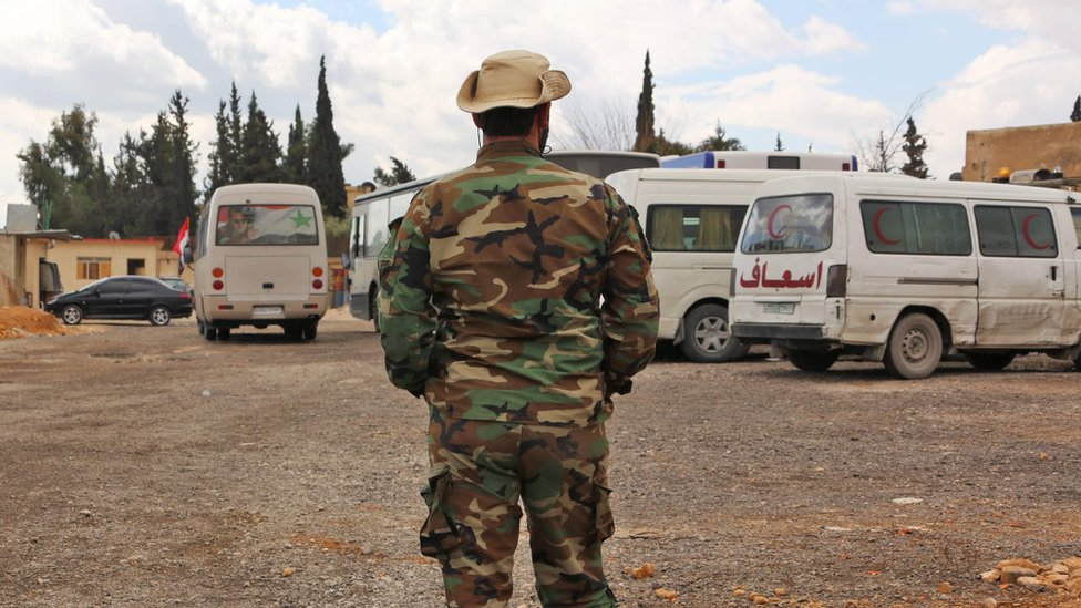 Syrian pro-government fighter stands near ambulances at the government-controlled al-Wafideen checkpoint, near the besieged rebel-held Eastern Ghouta (27 February 2018)