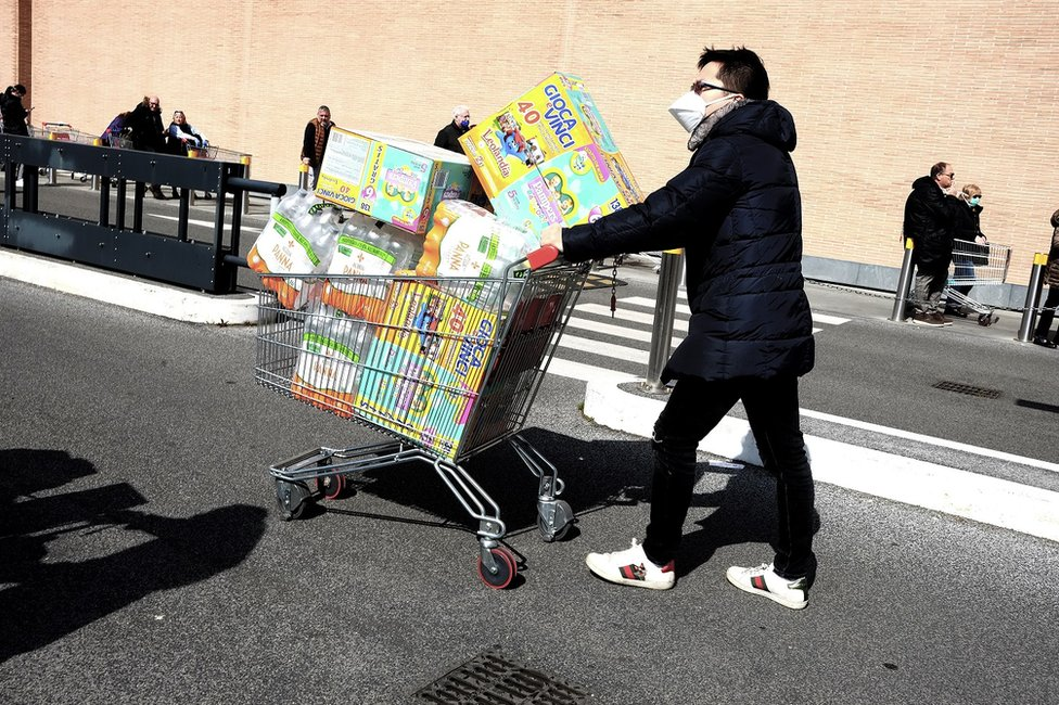 A man with a shopping trolley piled high with food