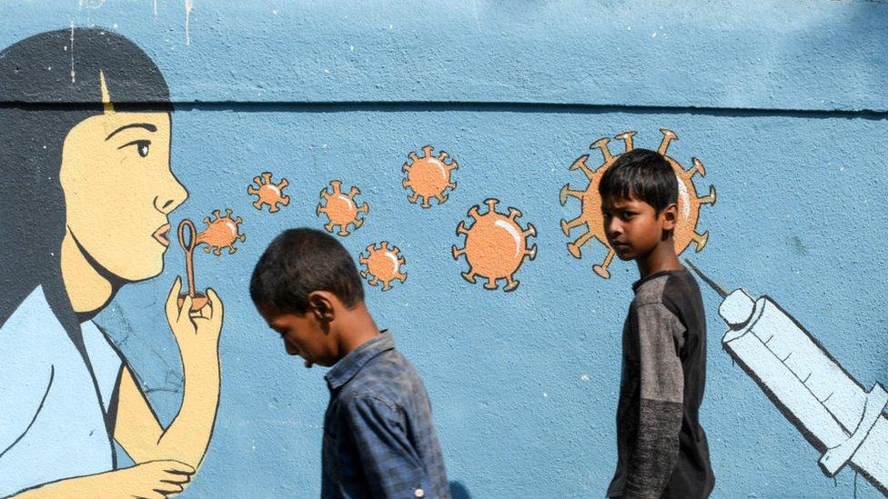 Hindistan'da koronavirüs resminin önünde yürüyen çocuklar.