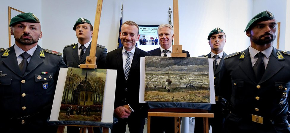 """Unsmiling officers flank a beaming Dutch museum curator as the paintings """"Congregation Leaving The Reformed Church of Neunen"""" and """"The Beach At Scheveningen During A Storm"""" by Vincent Van Gogh are displayed during an Italian investigators' press conference in Naples (30 September 2016)"""