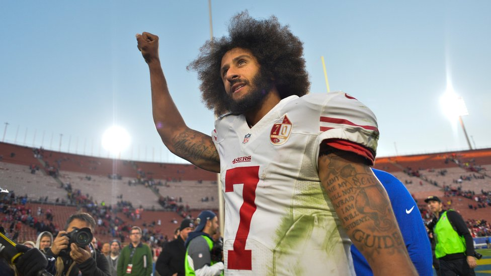 Colin Kaepernick pumps his fist as he acknowledges the cheers at Los Angeles Memorial Coliseum in Los Angeles