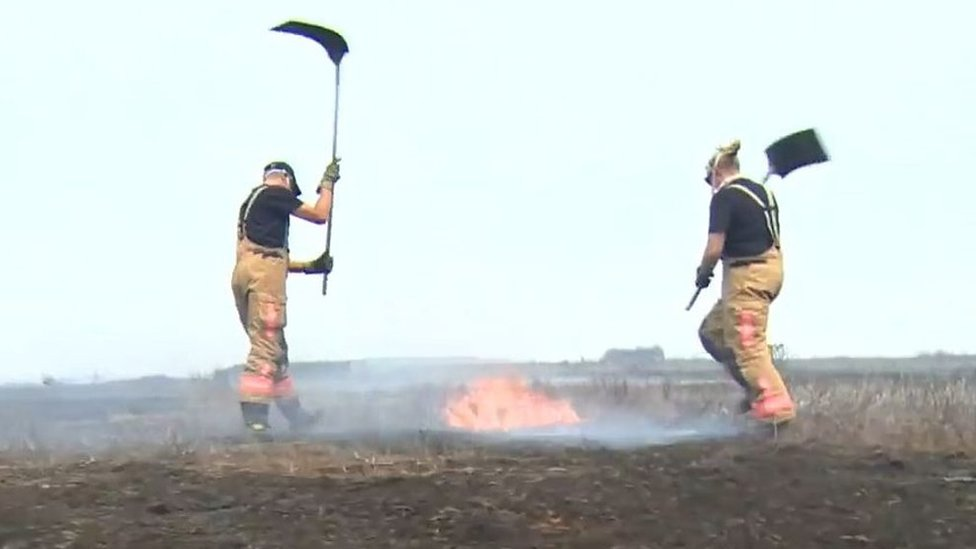 Firefighters beating flames on Saddleworth Moor