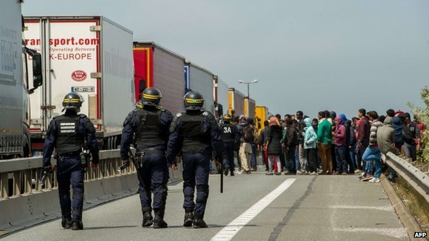 French riot police approach a crowd of migrants