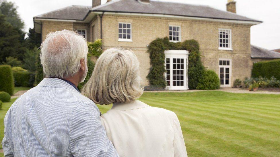 بيت كبير ورجل وامرأة يتطلعان إليه.