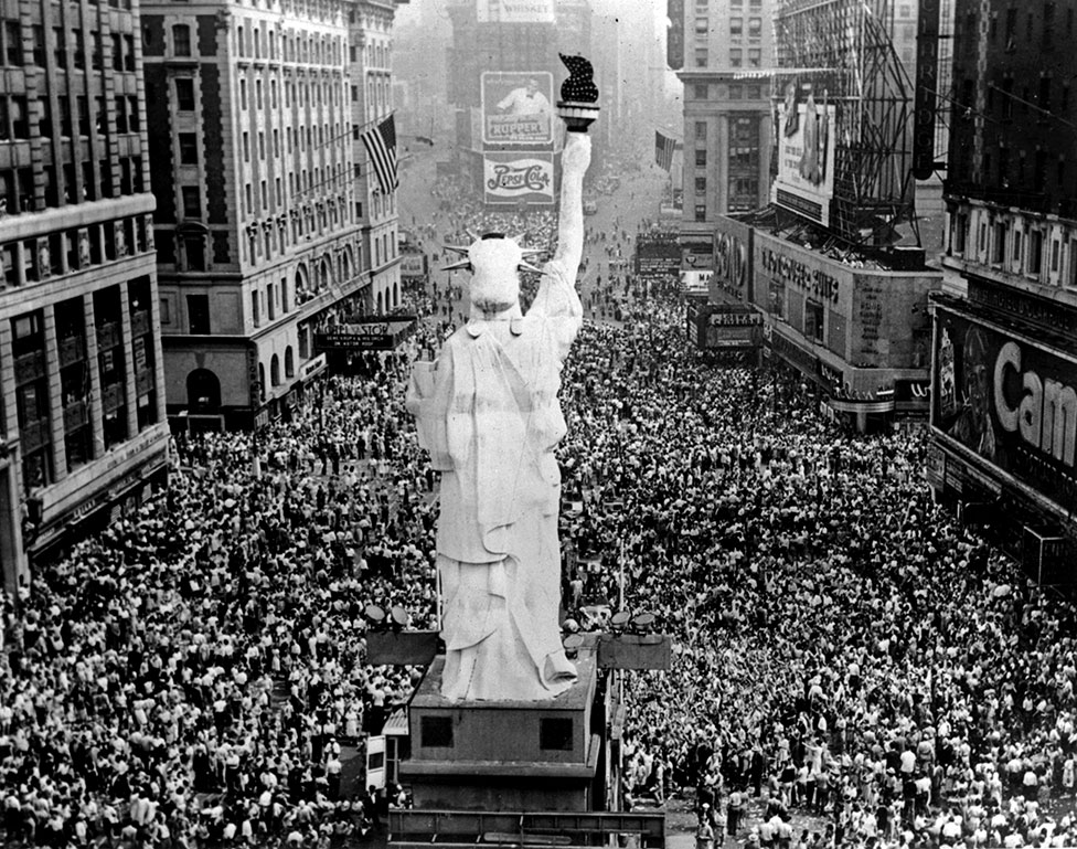 A scaled-down version of the Statue of Liberty is surrounded by cheering crowds