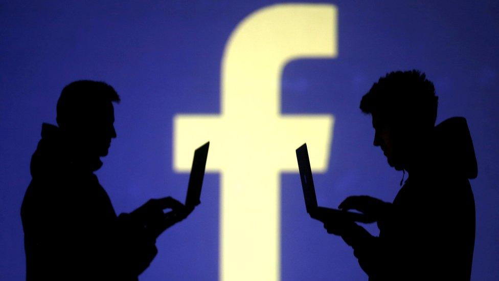 Facebook logosu önündeki bilgisayar kullanıcıları