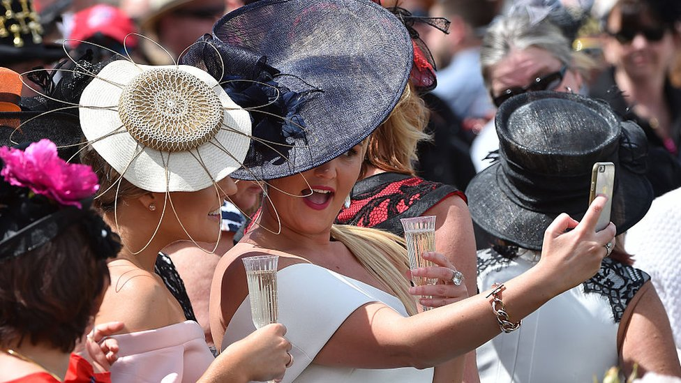 Dressed-up racegoers wearing elaborate hats pose for a selfie at the Melbourne Cup in 2018
