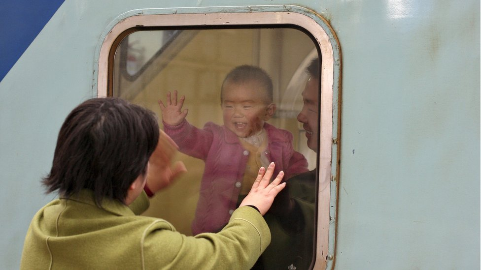 A Chinese baby waves to her mother