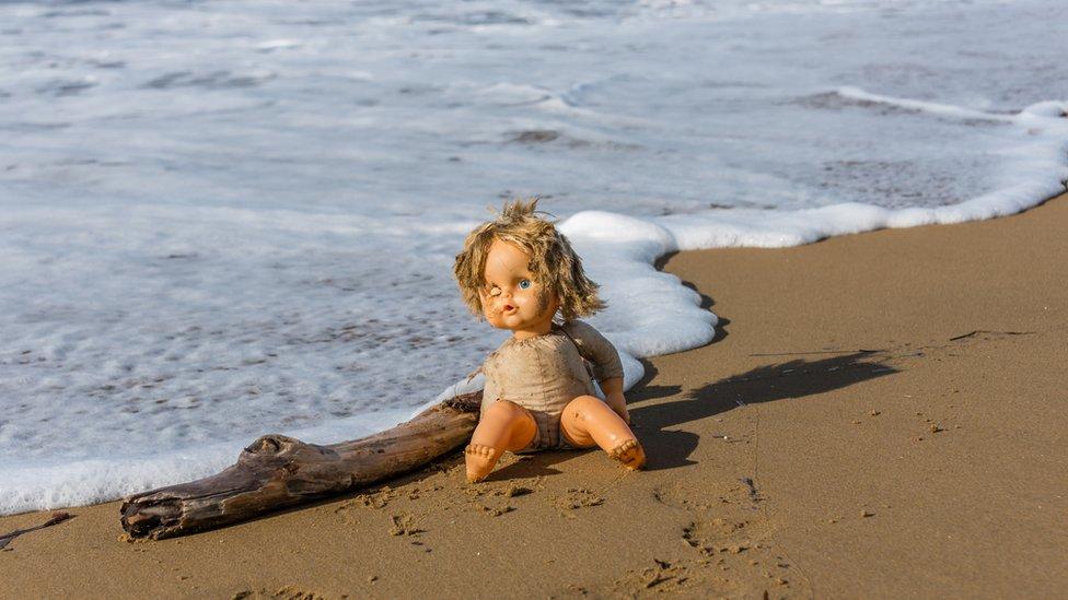 Muñeca abandonada en la orilla del mar.