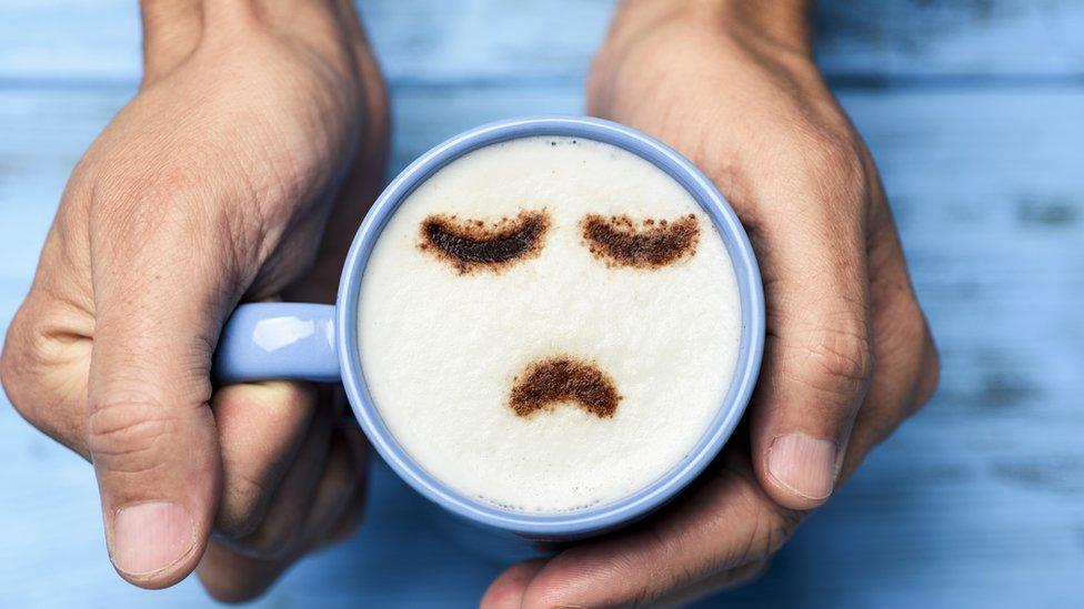 Una taza de café con un cara triste