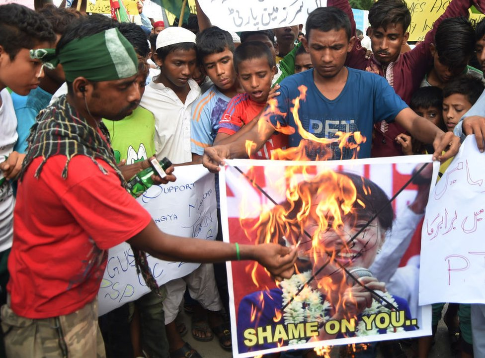 Pakistani demonstrators burn a placard featuring an image of Aung San Suu Kyi during a protest in Karachi on 6 September 2017