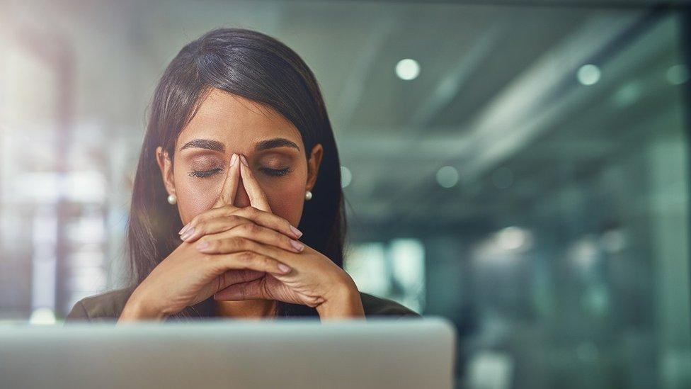 Mujer estresada delante de su laptop