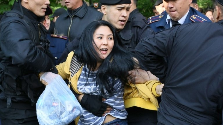 """Kazakh police officers detain opposition protesters in Almaty on May 1, 2019. - Dozens of protesters opposed to Kazakhstan""""s authoritarian regime were arrested by police in the largest city Almaty on Wednesday after decrying a snap election critics liken to a succession plan."""