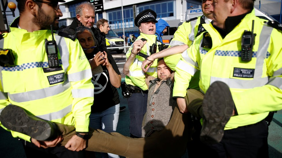 A protester is carried away by police during a demonstration at London City Airport