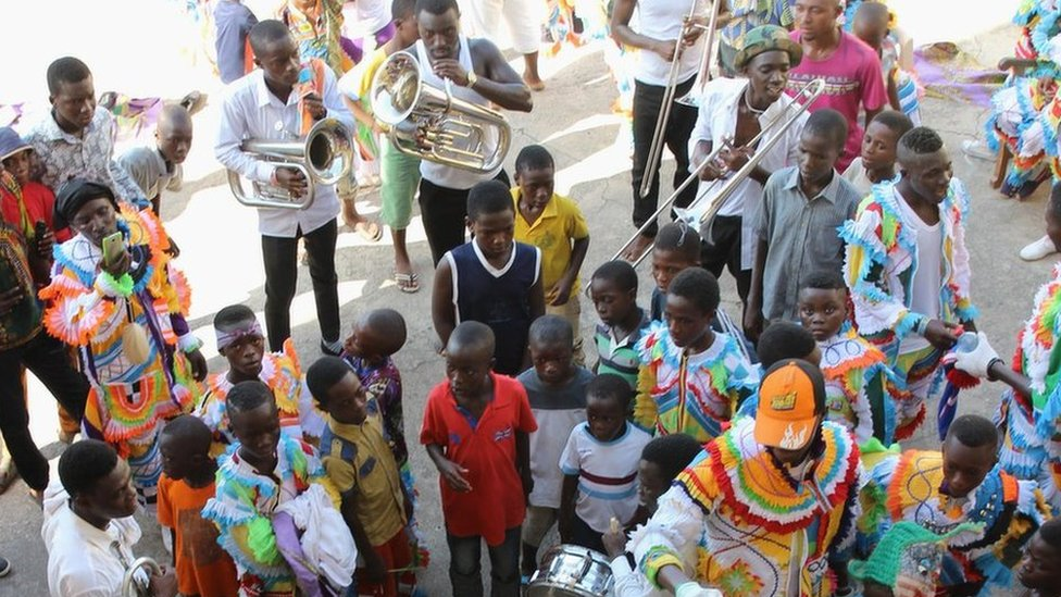 Men carry trumpets, surrounded by a group of young children, before the start of the parade in Sekondi Ghana