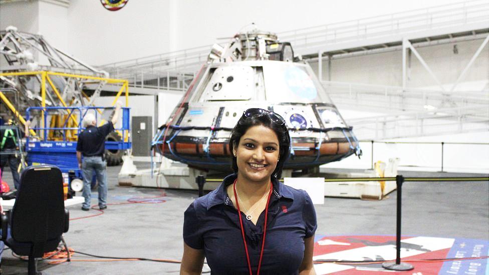 La Dra Varsha Jain frente a un módulo Orion en Centro Espacial Johnson de la NASA
