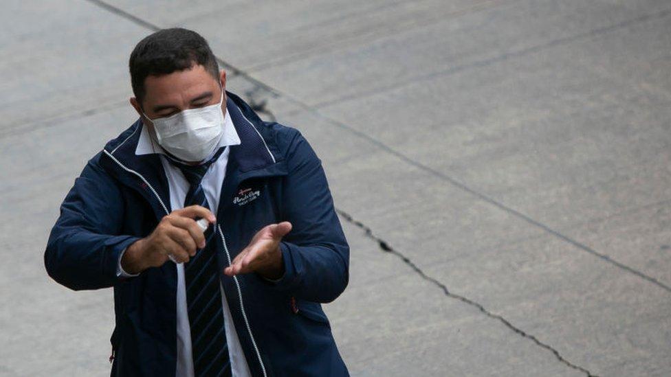 Un hombre con tapabocas rociandose gel antibacterial