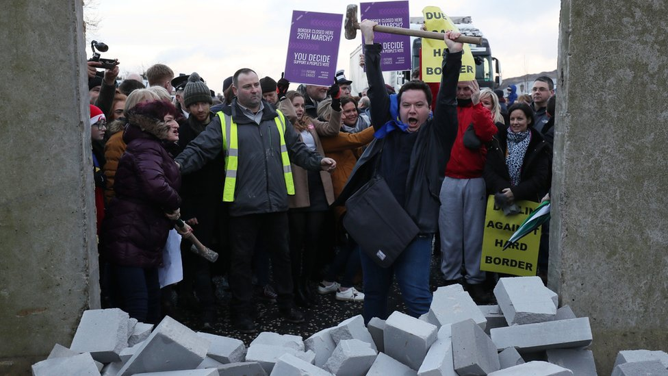 A man cheers after knocking dock a mock border wall at a Brexit protest near Newry