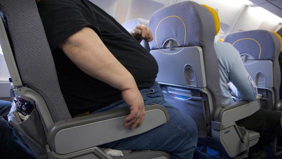 pasajero acomodándose en su asiento de avión
