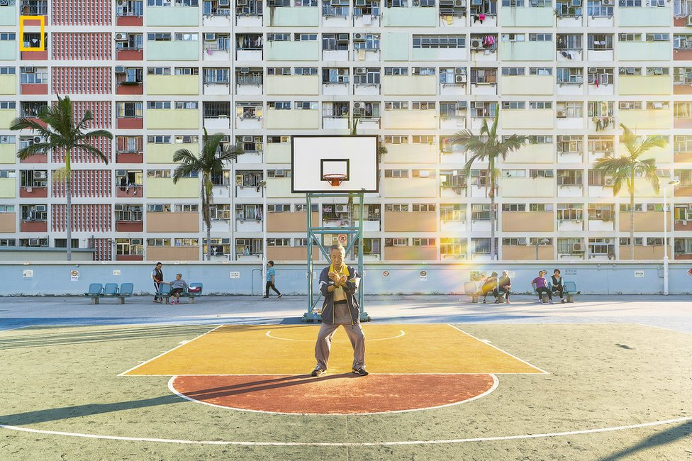 A man performs tai chi in front of a block of flats