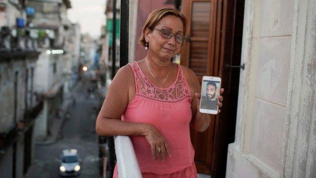 Raiza, la madre de Anyelo Troya, muestra una foto de su hijo en un celular